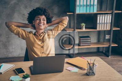 Obraz Photo of corporate cheerful positive ceo in yellow shirt smiling toothily dreaming thoughtful looking away relaxing after hard-working day