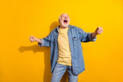 Obraz Photo of happy excited crazy cheerful smiling grandfather dancing screaming enjoying free time isolated on yellow color background