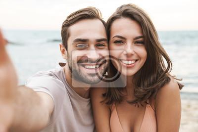 Obraz Photo of joyful young couple smiling and taking selfie photo