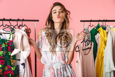 Obraz Photo of trendy woman near wardrobe with clothes choosing what to wear