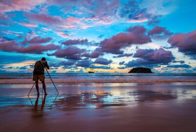 Photographer shooting image on the beach with color of the sunset in twilight