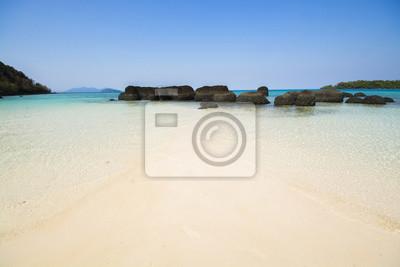 Piasek plaża z jasną wodą morską i niebieskim niebem. Tam są kamienie przy plażą .Island w zatoce Tajlandia.