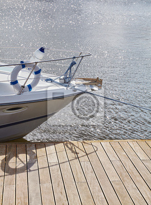 Picture of a boat bow moored to a pier in marina.