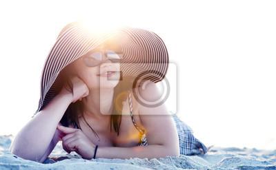 Piękna brunetka dziewczyna na piasku na plaży w czasie wschodu słońca.