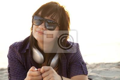 Piękna brunetka dziewczyna ze słuchawkami na piasku plaży.