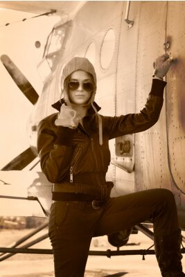 Obraz Piękna dziewczyna w płaszczu stoi obok samolotów wojennych.