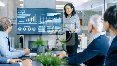 Obraz Piękna kobieta daje raport / prezentację swoim współpracownikom w sali konferencyjnej, pokazuje grafikę, wykresy kołowe i rozwój firmy na ścianie telewizora.