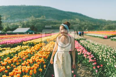 Obraz Piękna kobieta idąca przez pole tulipanów na wiosnę.