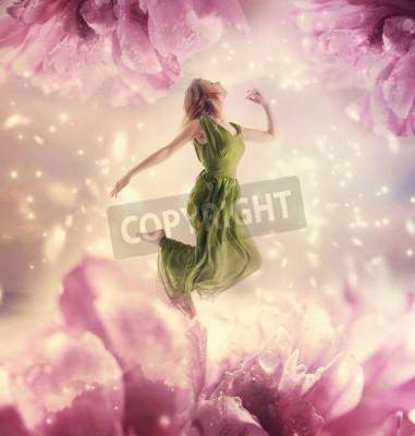 Obraz Piękna młoda kobieta skoków na gigantyczny kwiat