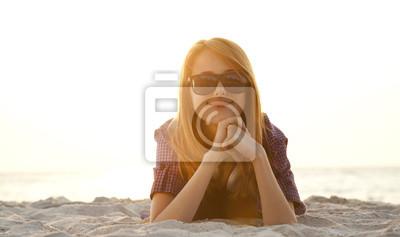 Piękna ruda dziewczyna ze słuchawkami na piasku plaży.