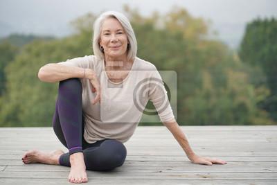 Obraz Piękna starsza kobieta siedzi outdoors w sportowej