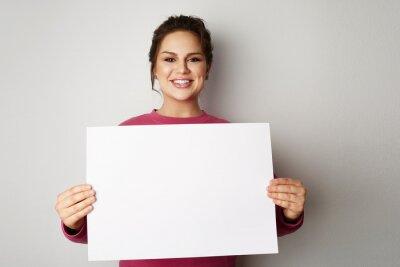 Obraz Piękne uśmiechnięte młode kobiety z sztandaru znakiem z białym pustym miejscem opuszczają papierowego billboard z kopii przestrzenią dla teksta nad szarym tłem