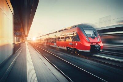 Piękny dworzec kolejowy z nowoczesnym czerwonym pociągiem podmiejskim w słońc