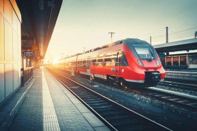Piękny nowoczesny dworzec kolejowy z dużą prędkością pociągu podmiejskim czerwone w kolorowe słońca. Kolej z rocznika tonowania. Pociąg na peronie. Koncepcja przemysłowe. turystyka kolejowa