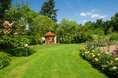 Obraz Piękny ogród z kwitnących róż, cegła ścieżki i małej altance