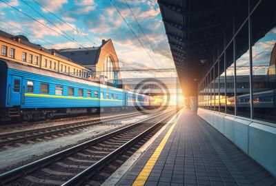 Piękny pociąg z błękitnymi furgonami przy stacją kolejową przy zmierzchem. Przemysłowy widok z nowoczesnym pociągiem, kolej, platforma kolejowa, budynki, niebo z chmurami w słoneczny wieczór. Turystyk