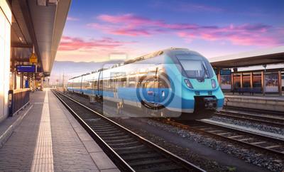 Piękny widok z nowoczesnych dużych prędkości pociągu na stacji kolejowej i kolorowe niebo z chmur na zachodzie słońca w Europie. Krajobrazu przemysłowego z niebieskim pociągu na platformie kolejowej.