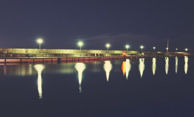 Pier at the port of Sassnitz at night, color toned picture, Germany.
