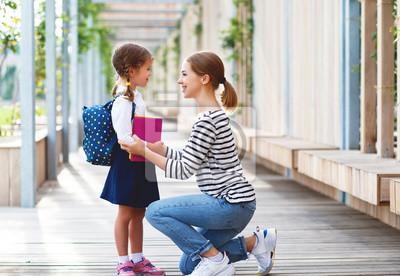 Obraz pierwszy dzień w szkole. matka prowadzi małe dziecko uczennice w pierwszej klasie.