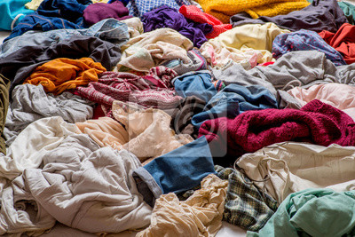 Obraz pile of used clothes on a light background. Second hand for recycling