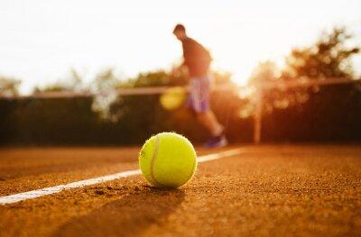 Obraz Piłka tenisowa i sylwetki gracza na korcie gliny