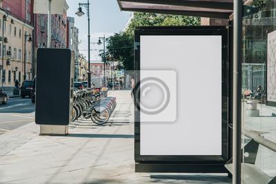 Obraz Pionowo pusty biały billboard przy przystanek autobusowy na ulicy miasta. W tle budynki i droga. Makieta. Plakat na ulicy obok jezdni. Słoneczny letni dzień.