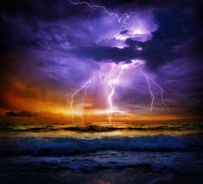 Obraz piorunami burza na morzu i na zachodzie słońca - zła pogoda