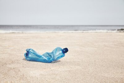 Plastic bottle on a beach, selective focus, color toning applied.