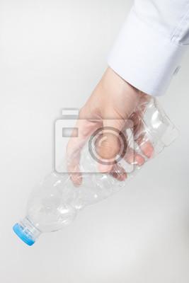 Plastikowa butelka skręt w działalności człowieka dłoni na białym tle.