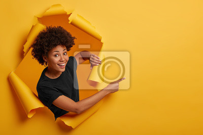 Obraz Pleased dark skinned Afro American woman stands in ripped background, laughs happily, poses in paper hole, points on right side, isolated on yellow wall. Space for your advertising or promotion.