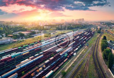 Pociągi towarowe. Widok z lotu ptaka kolorowych pociągów towarowych. Stacja kolejowa. Wagony towarowe na torach kolejowych. Przemysł ciężki. Scena przemysłowa z pociągów, budynki miejskie i pochmurne