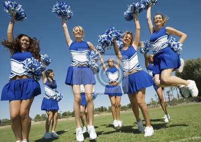 Obraz Podekscytowany młody cheerleaders z pompony doping na polu