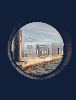 Port widziany przez stary iluminator statku z zastosowanym tonowaniem kolorów.