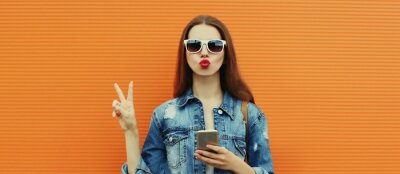 Obraz Portrait close up of young woman with smartphone wearing a denim jacket posing on an orange background