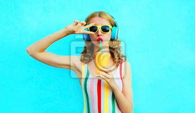 Obraz Portrait cool girl drinking fruit juice listening to music in wireless headphones on colorful blue background