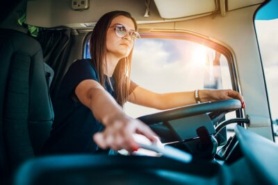 Obraz Portrait of beautiful young woman professional truck driver sitting and driving big truck. She is dangerously trying to take smart phone while driving.