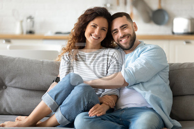 Obraz Portrait of couple posing photo shooting seated on couch indoors