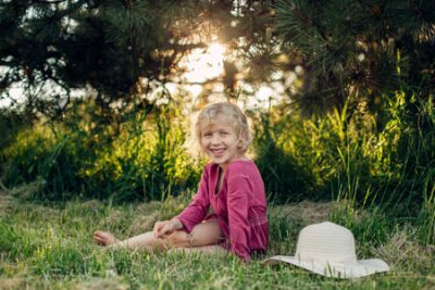 Obraz Portrait of cute beautiful blonde Caucasian girl in red pink dress with messy untidy hair sitting on ground grass in park outdoor at sunset. Happy adorable barefoot child kid enjoying summertime.