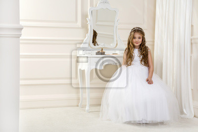 Obraz Portrait of cute little girl on white dress and wreath on first holy communion background church gate - Image. Young  model in the white communion dress stands in an elegant palace