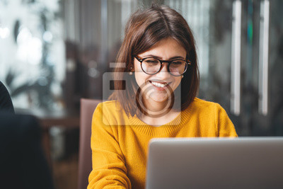 Obraz Portrait of happy business woman wearing glasses at workplace in office. Young handsome female worker using modern laptop