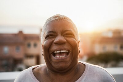 Obraz Portrait of happy senior african woman smiling on camera outdoor in the city - Focus on face