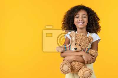 Obraz Portrait of smiling african girl hugging teddy bear toy isolated on yellow background