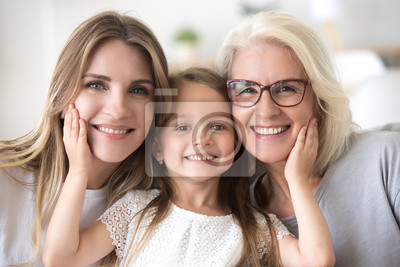 Obraz Portrait of three generations of women look at camera posing for family picture, cute little girl hug mom and granny enjoy time at home, smiling mother, daughter and grandmother spend weekend together
