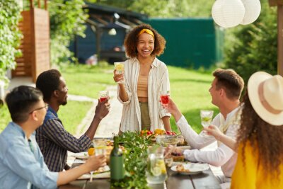 Obraz Portrait of young African-American woman laughing cheerfully while enjoying dinner with friends at outdoor terrace in Summer, copy space