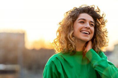 Obraz Portrait of young woman with curly hair in the city