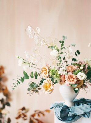 Obraz portrait shot of asymmetrical floral arrangement with blue linen