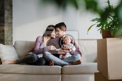 Obraz Portret młodej pary z dzieckiem i kartonami przeprowadzkami do nowego domu.