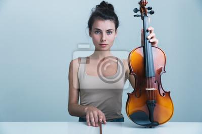 Obraz Portret pięknej młodej kobiety siedzącej przy stole