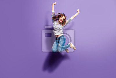 Obraz Portret rozochocony pozytywny dziewczyny doskakiwanie w powietrzu z nastroszonymi pięściami patrzeje kamerę odizolowywającą na fiołkowym tle. Koncepcja energii ludzi życia