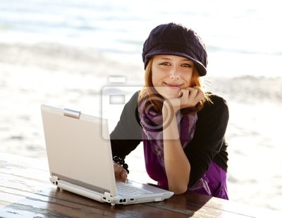 Portret rudowłosej dziewczyny z laptopem na plaży.
